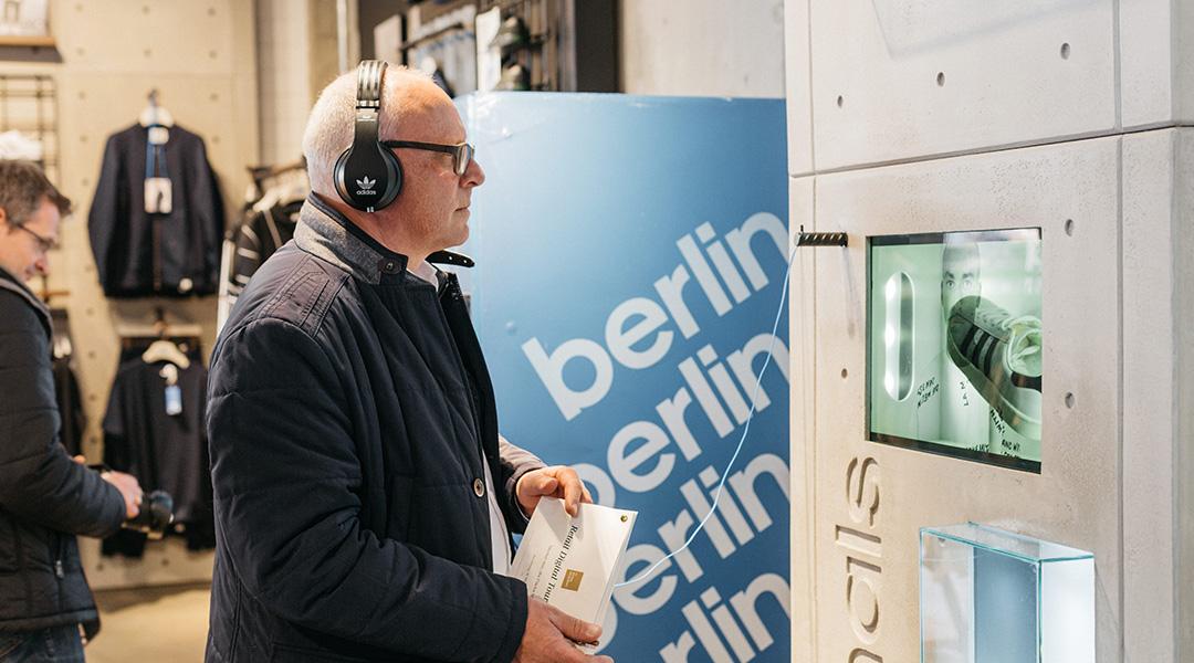 Älterer Mann steht mit Kopfhörern vor einem digitalen Screen in einem Laden