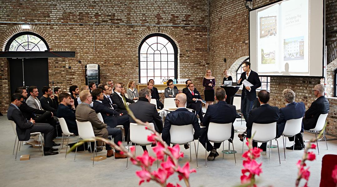 Kleine Gesprächsrunde lauscht der Präsentation eines Retail-Experten in einem Industrieloft