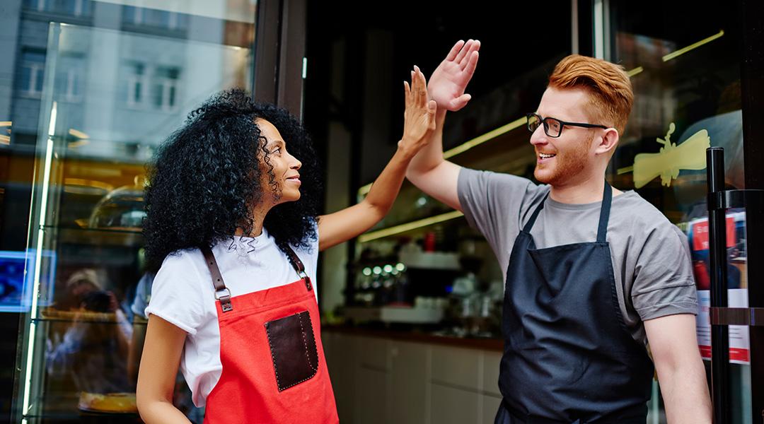 Zwei motivierte Mitarbeiter klatschen sich vor der Ladentür ab